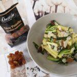 Pasta con zucchine, merluzzo, uva passita e mandorle a fettine